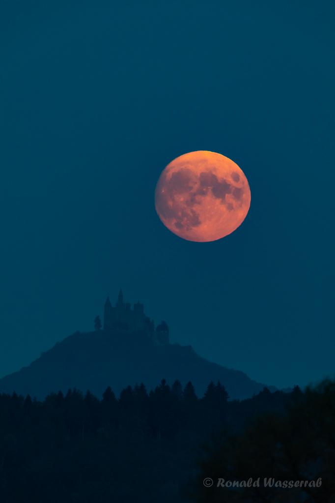 Der Mond schwebt über der Burg