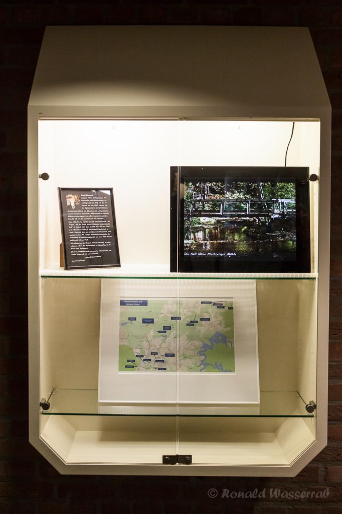 Vitrine mit Künstler-Portrait, Diaschau im digitalen Bilderrahmen und Karte der Aufnahmeorte